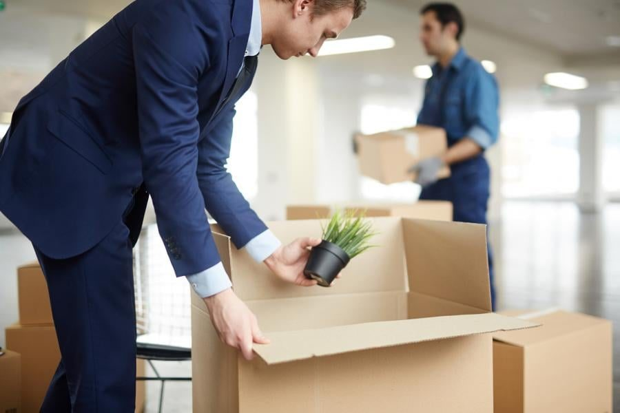 Office worker packing up a office moving box