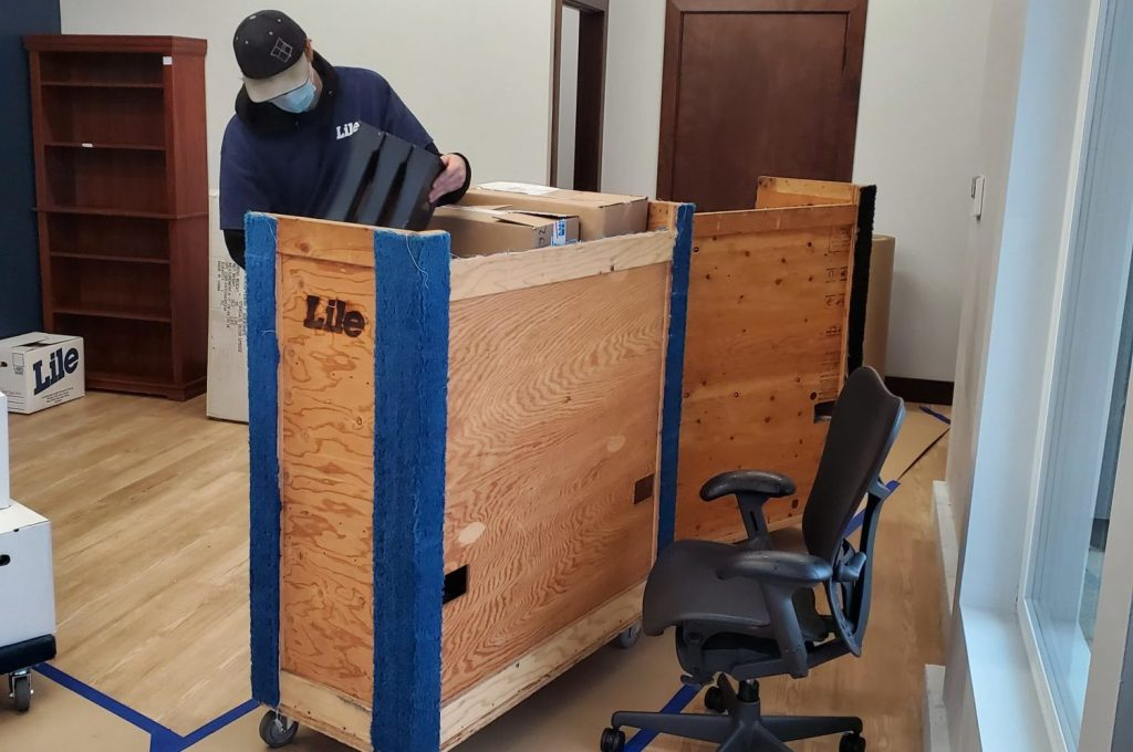 Office mover putting boxes on a moving cart.