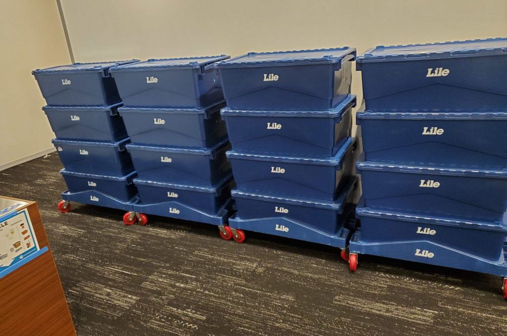 Stacked blue Lile e-crates on an office move
